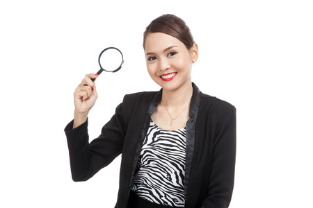 well dressed girl: Young Asian business woman with a magnifying glass  isolated on white background