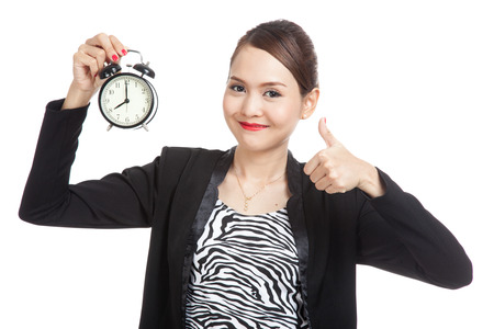 thumbs: Young Asian business woman show thumbs up with a clock  isolated on white background