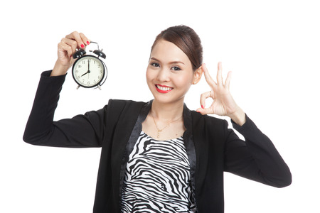 ok hand: Young Asian business woman show OK with a clock  isolated on white background Stock Photo