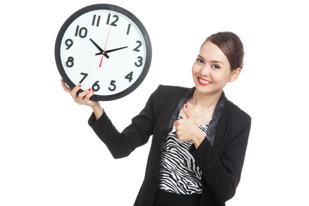 femme pouce leve: Young Asian business woman thumbs up with a clock  isolated on white background