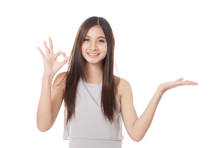 ok hand: Beautiful young Asian woman show palm hand and OK sign  isolated on white background