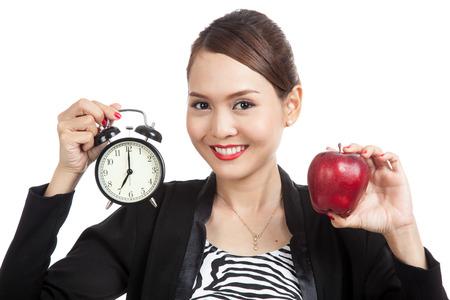 mujer trabajadora: Mujer de negocios asi�tica joven con la manzana roja y el reloj aislado en fondo blanco
