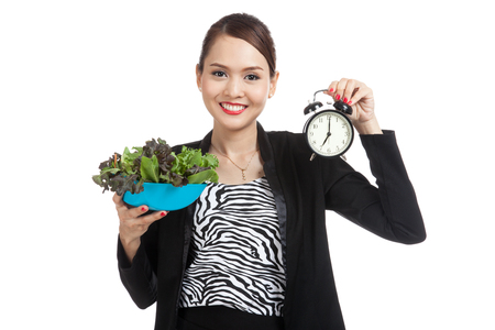 meal time: Young Asian business woman with clock and salad  isolated on white background