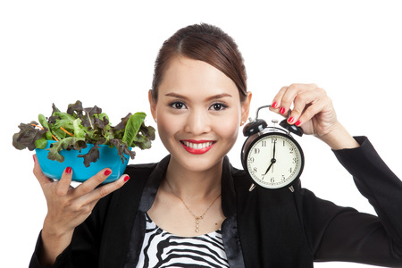 comiendo: Young Asian business woman with clock and salad  isolated on white background
