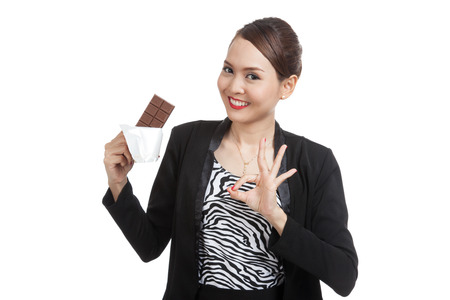 ok: Young Asian business woman show OK with chocolate bar  isolated on white background