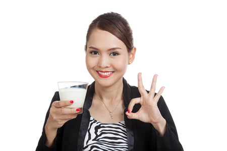 Healthy Asian woman drinking a glass of milk show OK sign  isolated on white background Stock Photo