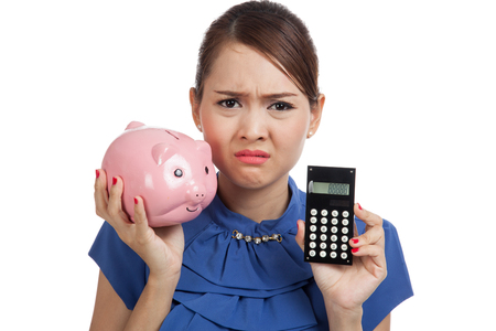 Unhappy Asian business woman with calculator and piggy bank  isolated on white background