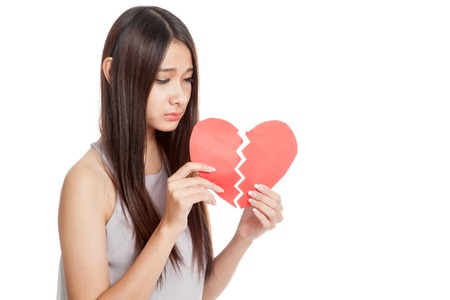 broken heart: Beautiful young Asian woman with broken heart  isolated on white background