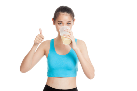 whey: Beautiful Asian healthy girl show thumbs up  drink whey protein  isolated on white background Stock Photo
