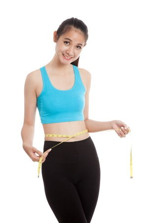 slim girl: Beautiful Asian healthy girl measuring her waist  isolated on white background Stock Photo