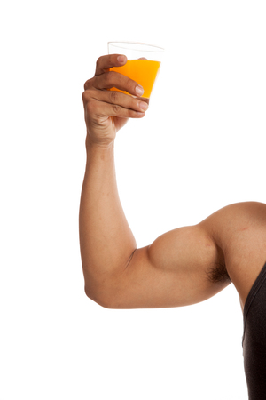 flexing: Muscular Asian mans arm  flexing biceps with orange juice