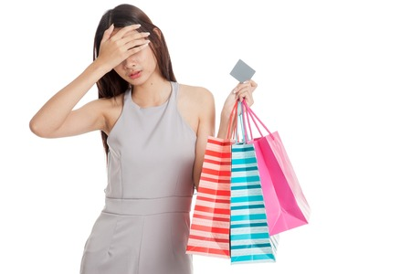 mood: Unhappy  young Asian woman with shopping bags and credit card  isolated on white background