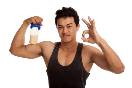 whey: Muscular Asian man  flexing biceps and show OK with whey protein  isolated on white background