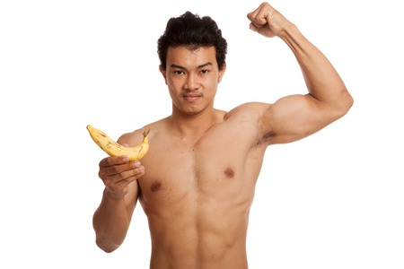 asian abs: Muscular Asian man flexing biceps with banana  isolated on white background Stock Photo