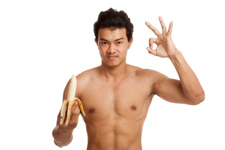 Muscular Asian man show OK with banana  isolated on white background