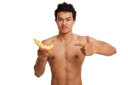 asian abs: Muscular Asian man point to banana  isolated on white background
