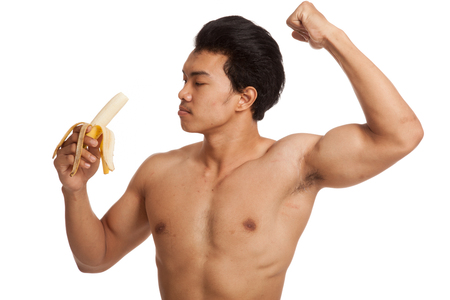 Muscular Asian man flexing biceps with banana  isolated on white background Stock Photo