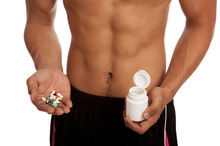 six pack: Muscular Asian man show  six pack abs  with some pills  isolated on white background Stock Photo