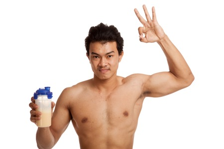 whey: Muscular Asian man  show OK sign with whey protein  isolated on white background Stock Photo