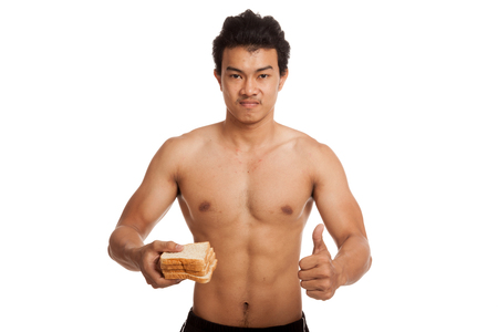 carbs: Muscular Asian man thumbs up load carbs with some bread  isolated on white background