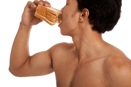 carbs: Muscular Asian man load carbs eat some bread  isolated on white background Stock Photo