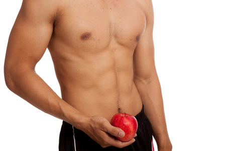 six pack: Muscular Asian man show six pack abs with red apple  isolated on white background Stock Photo