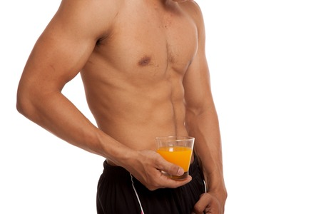 asian abs: Muscular Asian man show his six pack abs with orange juice  isolated on white background