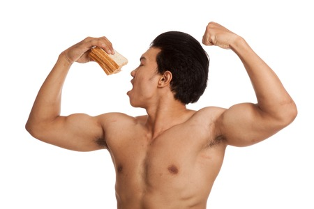 carbs: Muscular Asian man load carbs with some bread  flexing biceps  isolated on white background Stock Photo