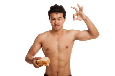 carbs: Muscular Asian man load carbs with some bread show OK  isolated on white background