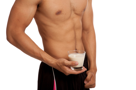 six pack: Muscular Asian man show his six pack abs with milk  isolated on white background Stock Photo