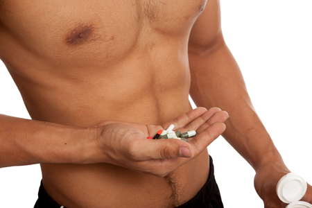 human body substance: Muscular Asian man show  six pack abs  with some pills  isolated on white background Stock Photo