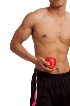 asian abs: Muscular Asian man show six pack abs with red apple  isolated on white background Stock Photo