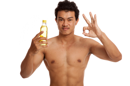 electrolyte: Muscular Asian man show OK  with electrolyte drink  isolated on white background