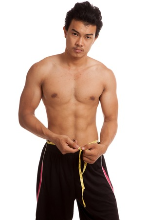 asian abs: Muscular Asian man with measuring tape  isolated on white background Stock Photo