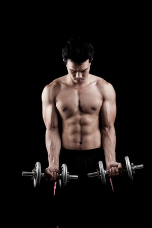 asian abs: Muscular Asian man with dumbbell on dark background Stock Photo