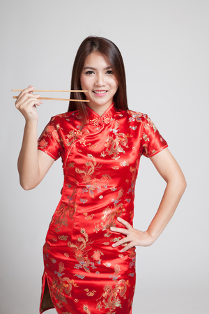 chipao: Asian girl in chinese cheongsam dress with  chopsticks on gray background Stock Photo