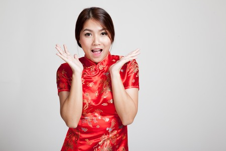 chipao: Excited Asian girl in chinese cheongsam dress on gray background