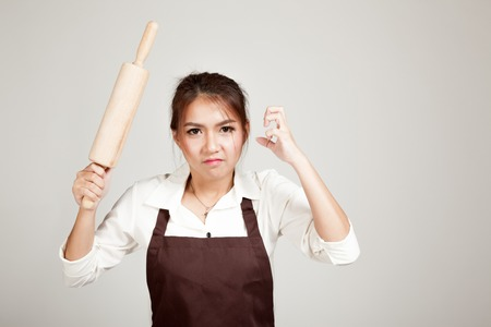 sulk: Asian Baker woman  in apron  with wooden rolling pin on gray background Stock Photo
