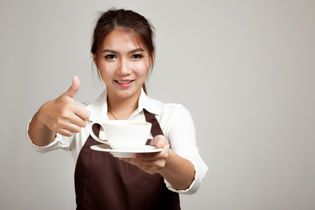 Waitress or barista  in apron thumbs up  holding coffee 스톡 콘텐츠