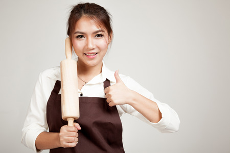 rolling up: Asian Baker woman  in apron   thumbs up  with wooden rolling pin on gray background