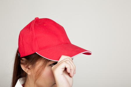 self assurance: Asian girl with red hat on gray background Stock Photo