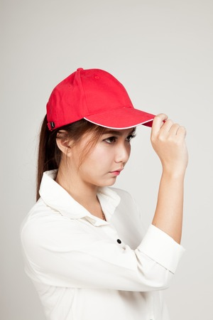 informal clothing: Asian girl with red hat on gray background Stock Photo