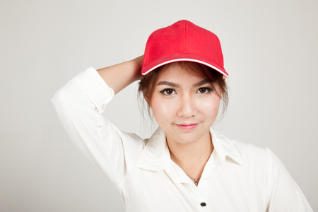 informal clothing: Happy asian girl with red hat on gray background