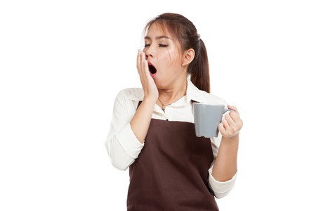Asian waitress  in apron yawn with cup of coffee  isolated on white background