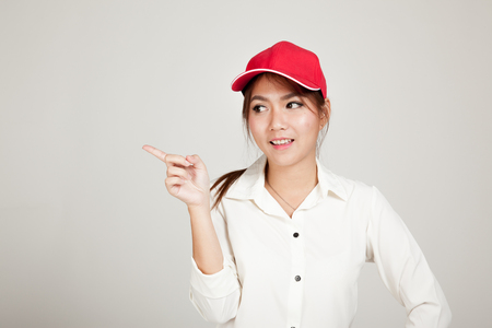 informal clothing: Happy asian girl with red hat point to blank space on gray background