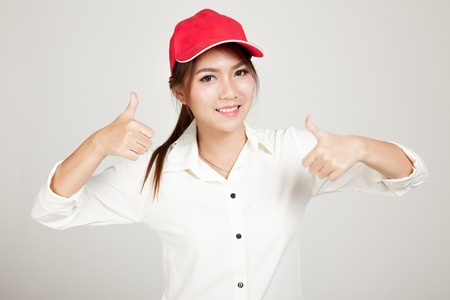 self assurance: Happy asian girl  thumbs up with red hat on gray background