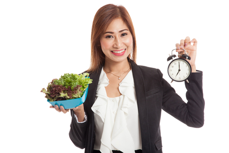 punctual: Young Asian business woman with clock and salad  isolated on white background