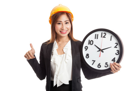 woman thumbs up: Asian engineer woman thumbs up with a clock  isolated on white background