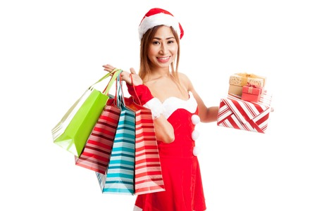christmas debt: Asian Christmas girl with Santa clothes,  gift box and shopping bag   isolated on white background