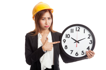 mood: Asian engineer woman in bad mood with a clock  isolated on white background Stock Photo